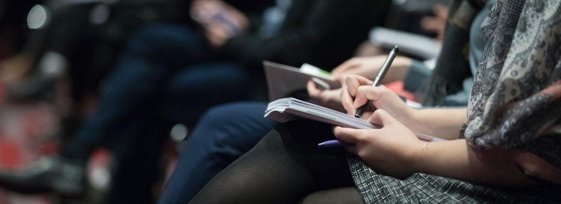 Image montrant des personnes prenant des notes pendant une conférence